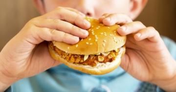 Bambino che mangia un panino con hamburger