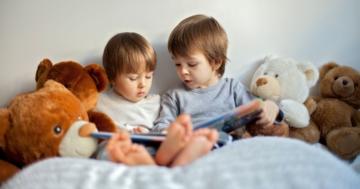 Due fratellini che leggono uno accanto all'altro