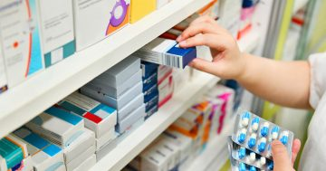 Una mano prende una confezione di medicine dallo scaffale di una farmacia