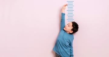 Bambino che misura la propria crescita in altezza