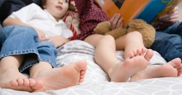 Bambini sdraiati sul letto ad ascoltare un racconto dei genitori
