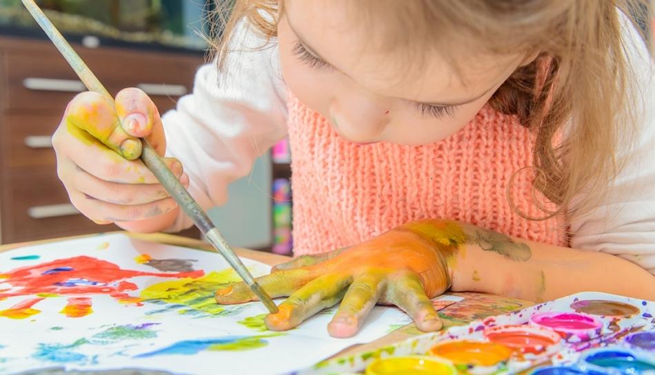 Bambina che gioca a scuola con i colori