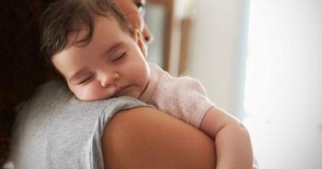 Bambino che dorme in braccio alla mamma