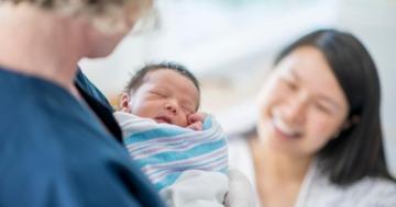 Una neomamma guarda sorridendo il bambino in braccio all'ostetrica