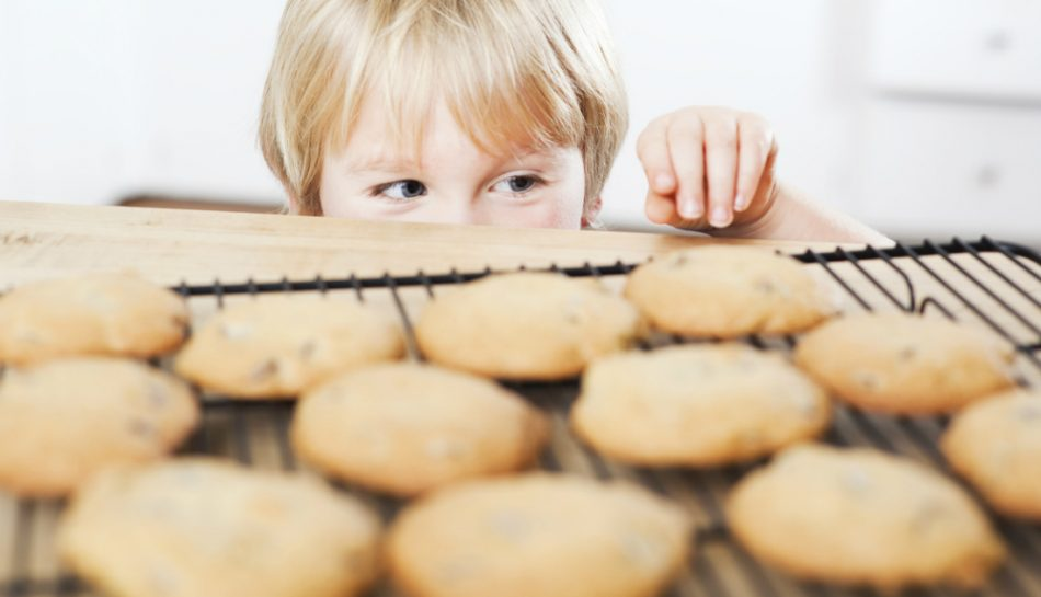 Bambino davanti a un'infornata di biscotti