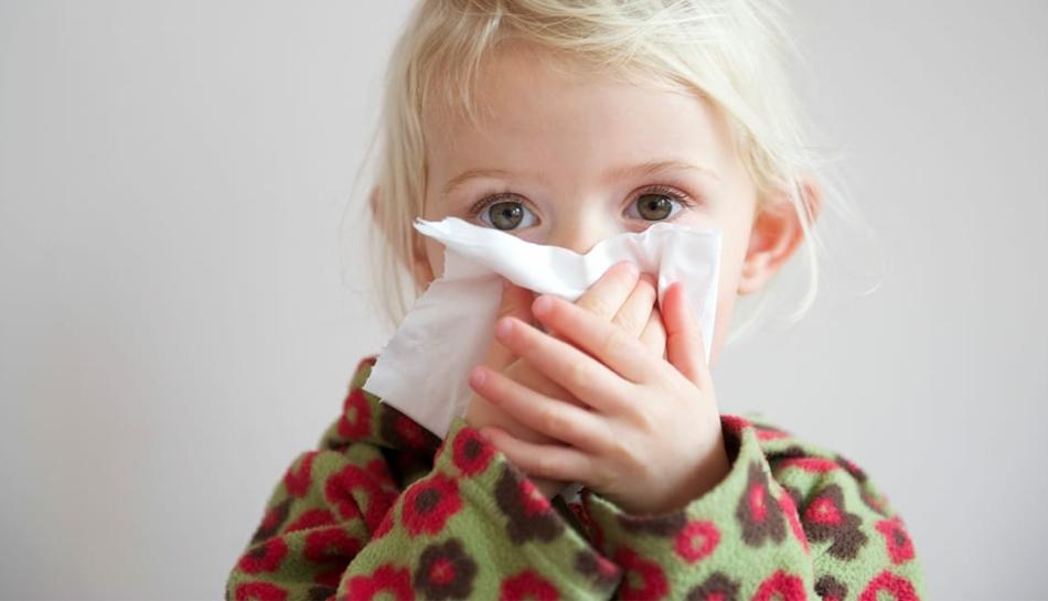 Bambina con il raffreddore che si soffia il naso