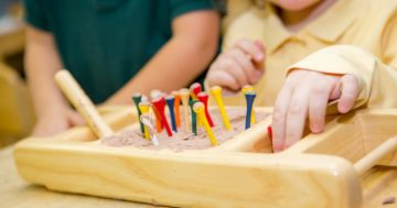 Bambino gioca con materiali sensoriali Montessori