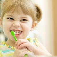 Una bambina che si lava i denti con dentifricio fatto in casa