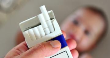 Bambino guarda un pacchetto di sigarette