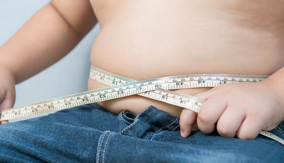 Primo piano della pancia di un bambino cinta da un metro