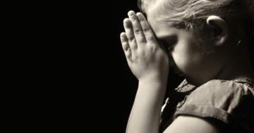 Bambina con le mangi giunte in preghiera