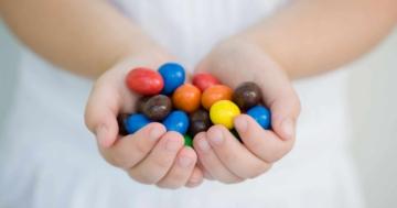 Mani di bambino che tengono in mano cioccolatini che favoriscono l'obesità