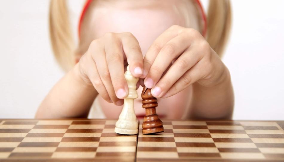 Bambina che muove gli scacchi e impara le regole