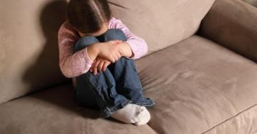 Bambina rannicchiata sul divano