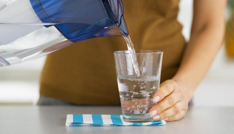 Donna che versa l'acqua da una caraffa filtrante