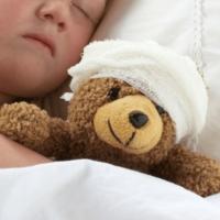 Bambina che stringe il suo peluche bendato: metafora del trauma cranico