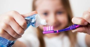 Bambina che mette del dentrificio sullo spazzolino