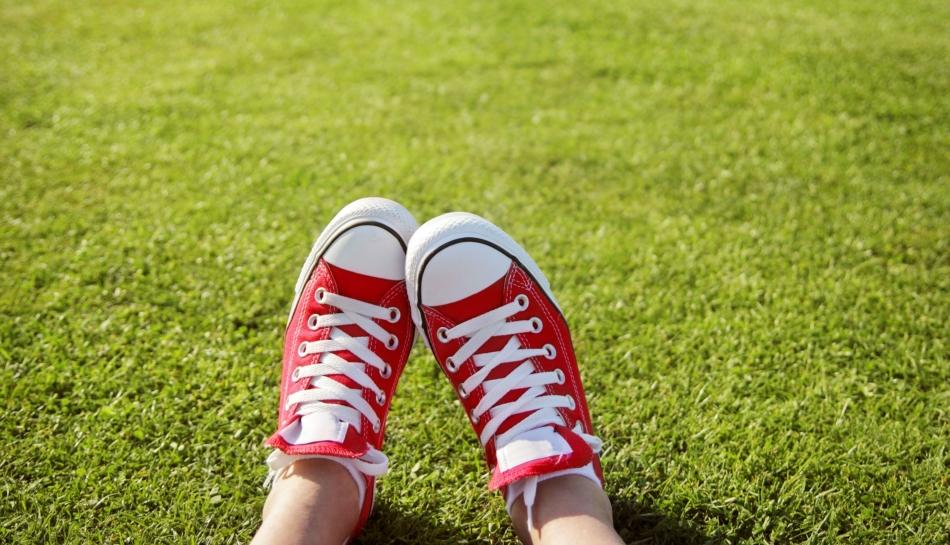 Primo piano di piedi di un adolescente sdraiato su un prato