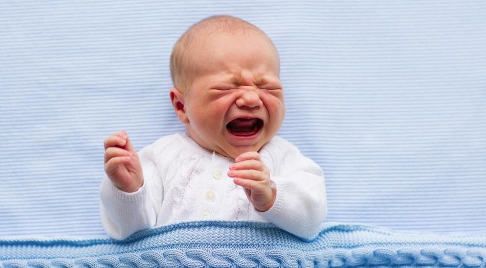 Un neonato che piange nella culla
