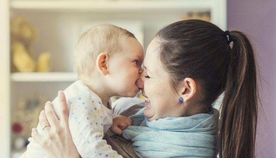 Bambino che morde il naso della mamma