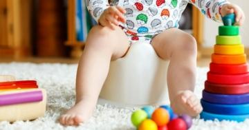 Primo piano di gambe di bambino senza pannolino seduto sul vasino
