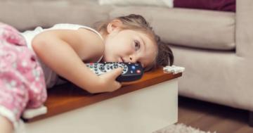 Bambina sdraiata sul divano con in mano il telecomando