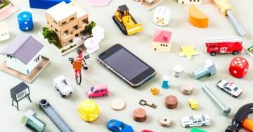 Giocattoli tradizionali che circondano uno smartphone, strumento di nuova tecnologia
