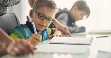 bambino fa compiti con maestra