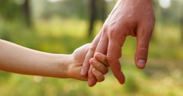 Bambino stringe la mano del padre