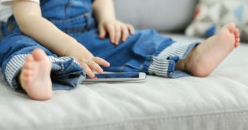 Bambino seduto sul divano che usa uno smartphone