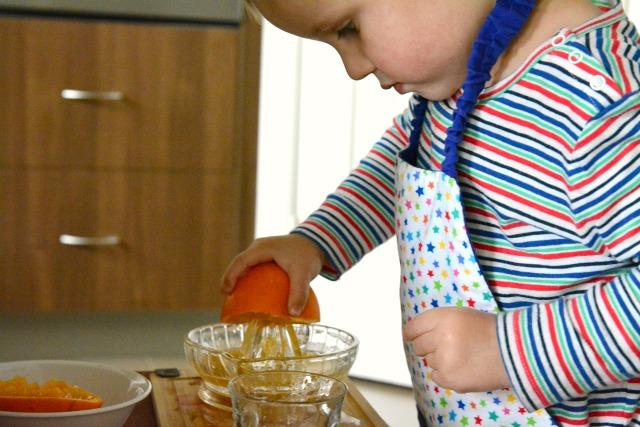 Bambino che spreme un'arancia