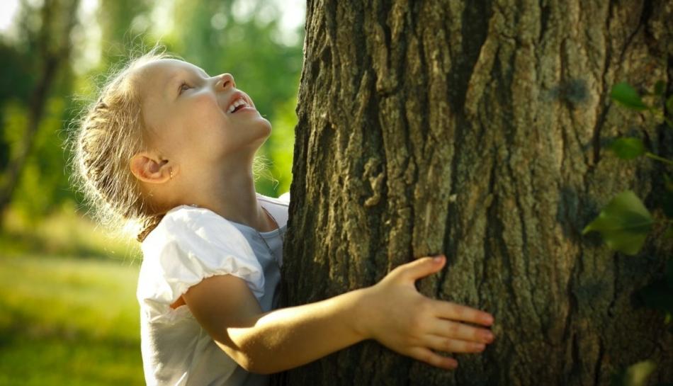 Bambina nella natura abbraccia un albero