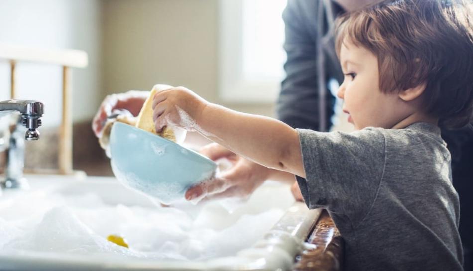 Bambino impara a lavare i piatti