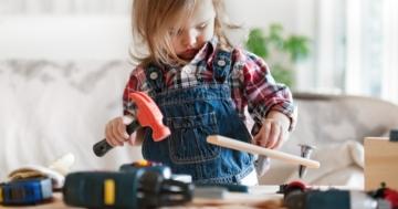 Bambina gioca con attrezzi da lavoro giocattolo