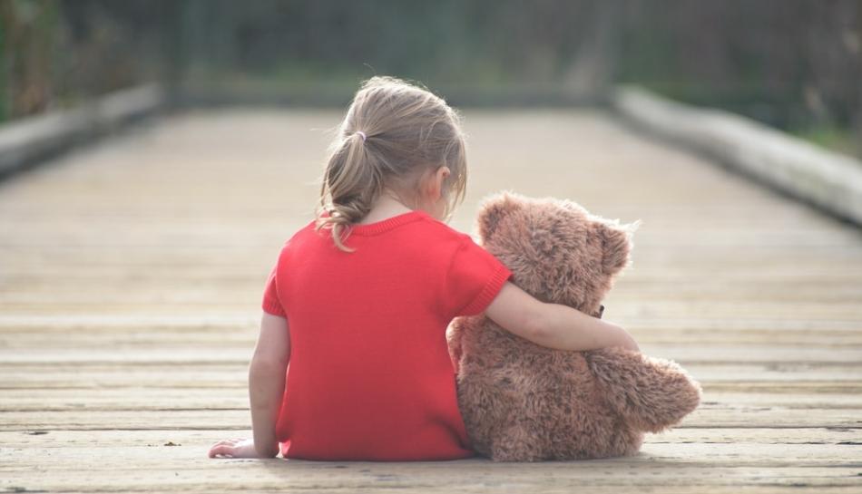 Bambina di spalle con il suo orsacchiotto