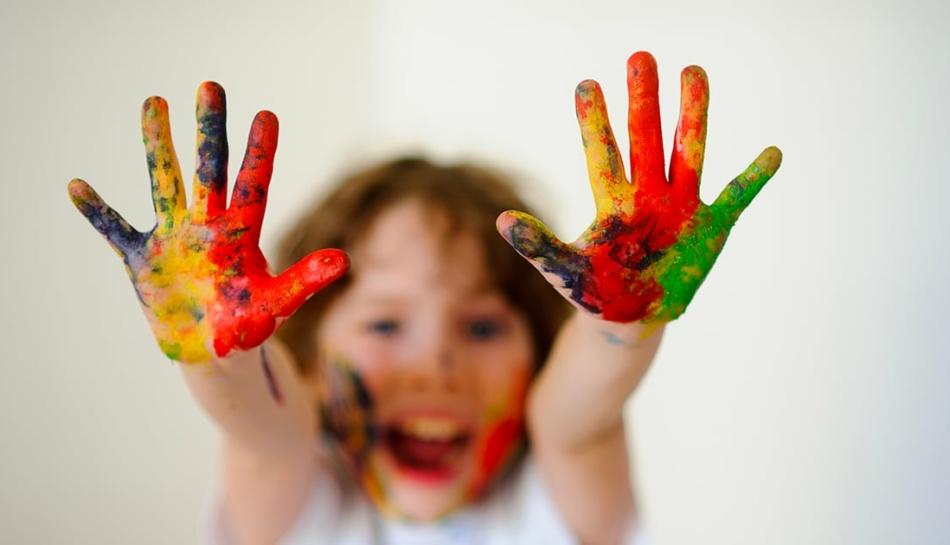 Bambino che mostra le mani colorate a regola d'arte