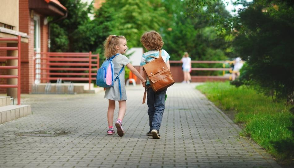 Bambini vanno a scuola tenendosi per mano