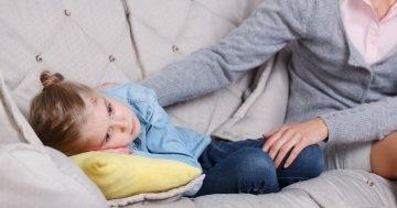 Bambina triste sdraiata sul divano
