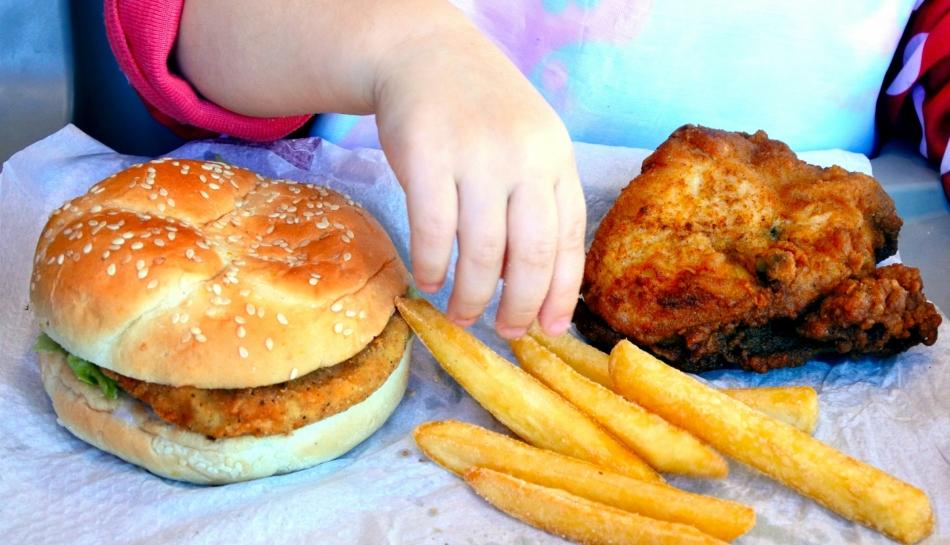 Mano di bambina seduta davanti a hamburger e patatine frette, ricche di acrilammide
