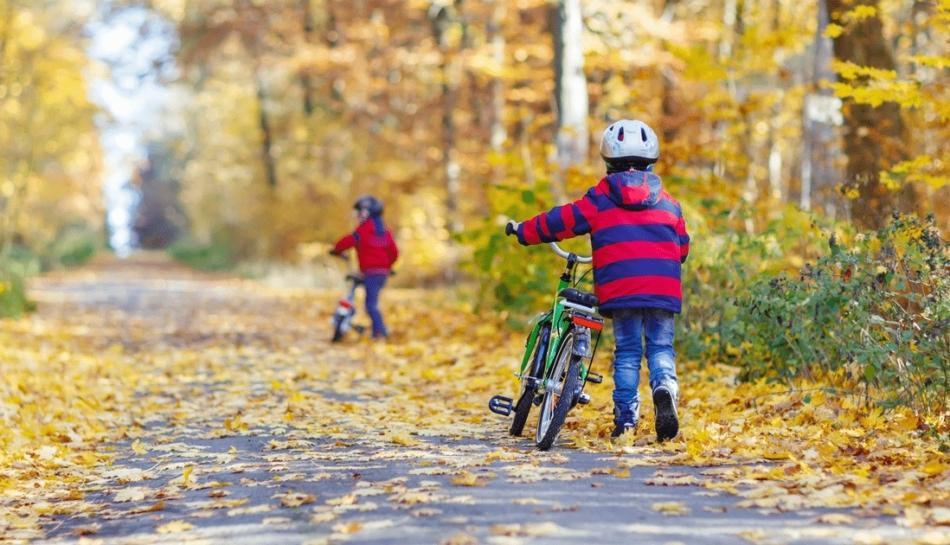 Bambini che si muovono a piedi portando la bici