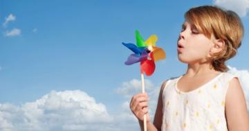 Bambina che soffia su una girandola colorata