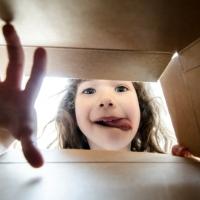 Bambina che osserva l'interno di una scatola e ci infila il braccio