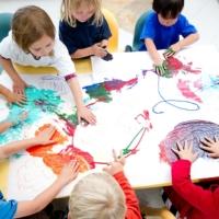 Bambini di un asilo che cooperano nel disegno