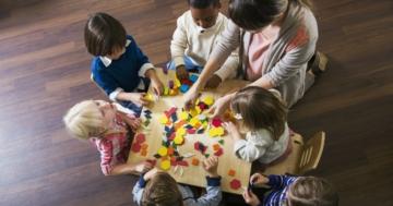 Bambini all'asilo intorno a un tavolo in una classe eterogenea