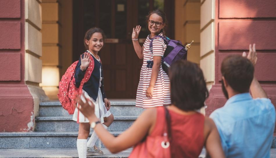 bambine entrano a scuola salutando genitori