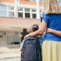 Mamma con due bambini all'ingresso a scuola