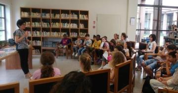 Bibliotecaria che parla di lettura a un pubblico di giovani