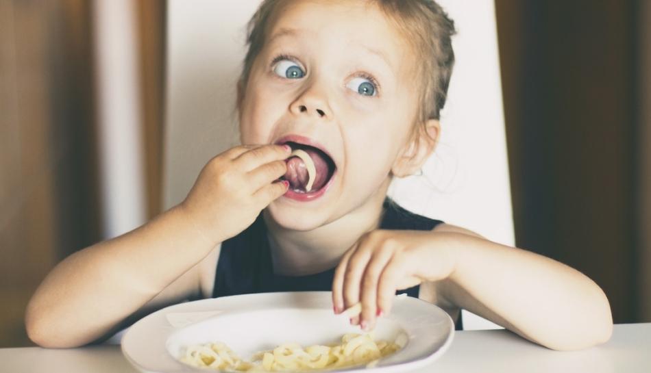 Bambina a tavola mangia la pasta con le mani