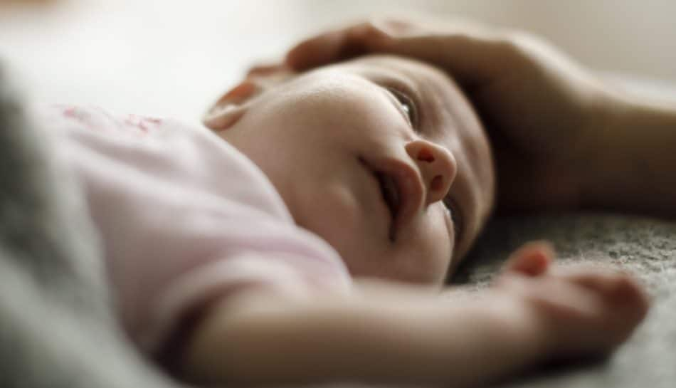 Bambino sdraiato che osserva il movimento di una carezza della madre