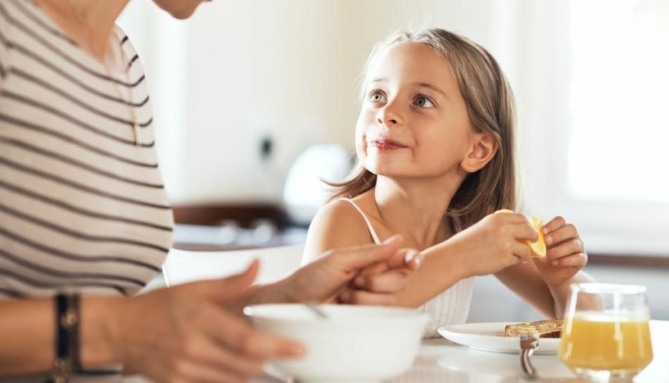 Bambina seduta a tavola a mangiare con la mamma